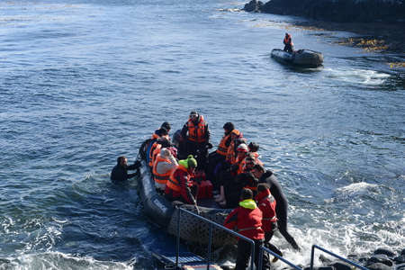 disembark: Tourists disembark from cruise ship on Cape horn.