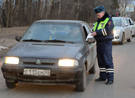 lieutenant: The inspector dorozhno-patrol service checks the documents of the driver of the car.
