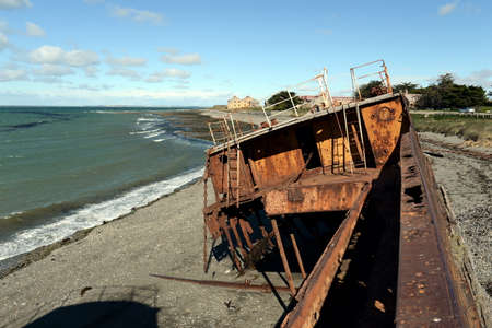 Rusty ship on the shore of the Strait of Magellan in the village of San Gregorio.