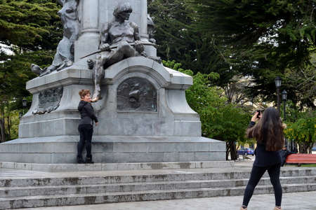 Tourists at monument to Fernando Magellan in Punta arenas.