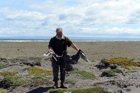 Ornithologist with a dead bird in the Gulf of Inutil.