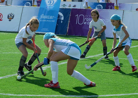 Girls play field hockey.