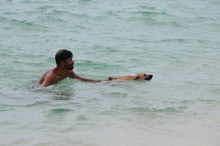 Lankan man bathes dog on the beach.