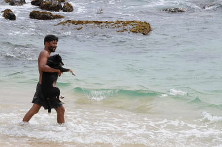 Lankan man bathes dog on the beach