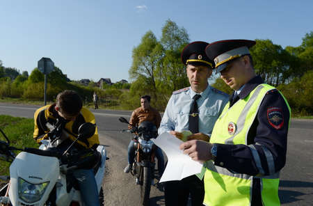Employees of traffic police draw up a Protocol on violation of traffic rules by motorcycle.