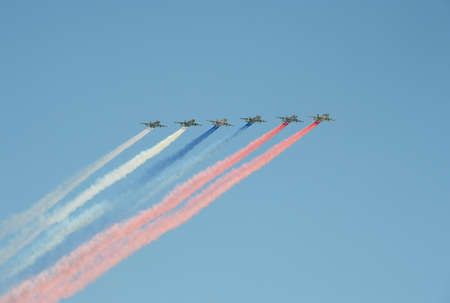 commemorate: A group of assault plane Sukhoi Su-25 Grach (NATO reporting name: Frogfoot) in the sky smoke flag of the Russian flag at the rehearsal of parade dedicated to Victory Day