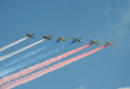 A group of assault plane Sukhoi Su-25 Grach (NATO reporting name: Frogfoot) in the sky smoke flag of the Russian flag at the rehearsal of parade dedicated to Victory Day