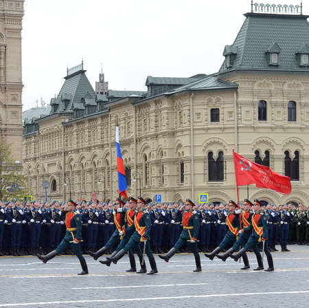 Soldiers of the honor guard special commandant of the Preobrazhensky regiment carry the Victory banner and the Russian flag at a military parade on a red square. 에디토리얼