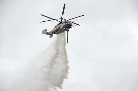 The fire helicopter КА-32А drops water.
