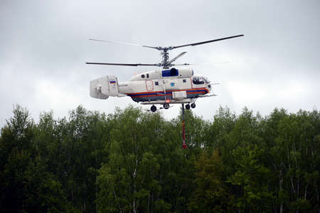 The fire-fighting helicopter КА-32 А pumps water.