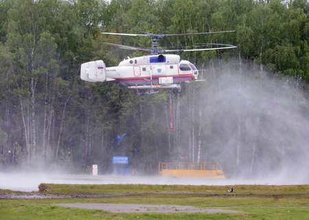 Fire-fighting helicopter KA-32 A recovers water from the reservoir at the training ground of the Noginsk rescue center of the Ministry of Emergency Situations of Russia.