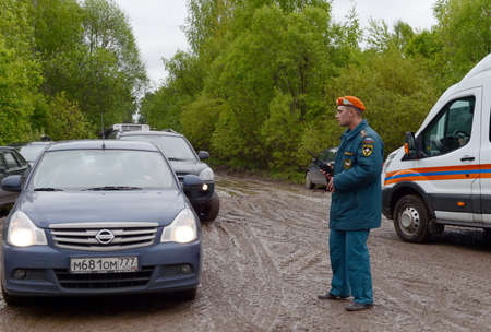 The employee of the Ministry of Emergency Situations of Russia regulates the movement of cars on the road near Moscow.