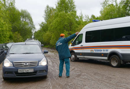 The employee of the Ministry of Emergency Situations of Russia regulates the movement of cars on the road near Moscow. Banco de Imagens - 84098536