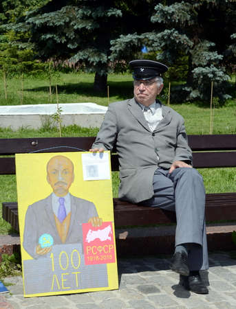 An unknown elderly man with a Communist poster on the Poklonnaya Hill of Moscow.