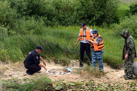 Police officers take out a fish from a fisherman for poaching on the Oka River.