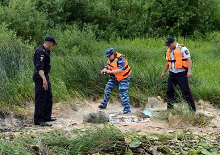警察官は、オカ川の密猟の漁師から魚を取り出します。