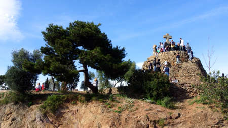 Tourists in Barcelona in the Park Guell at Calvary three crosses.