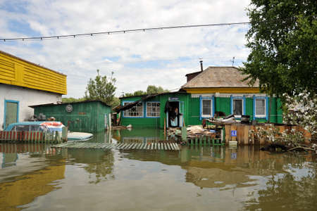 An unknown elderly woman in her home during a flood. The Ob river, which came out of the banks, flooded the outskirts of the city.