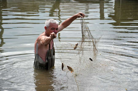 Local resident fishing network during the flood in the garden. Editorial