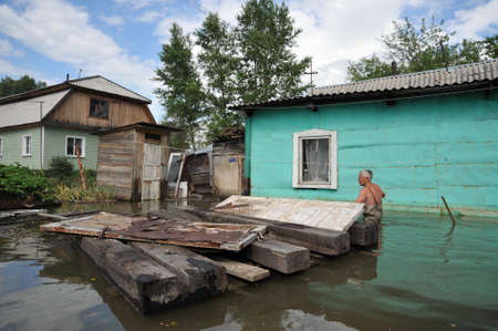 An unknown man on a flooded plot near his house. The river Ob, which emerged from the shores, flooded the outskirts of the city.