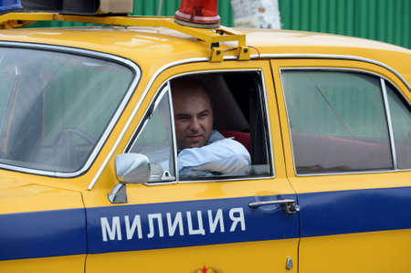 The officer of the road patrol service driving the GAZ-24 Volga police car