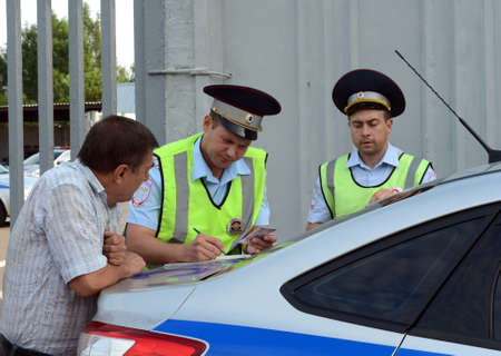 An inspectors of the road police patrol service makes a report on the violation of traffic rules.