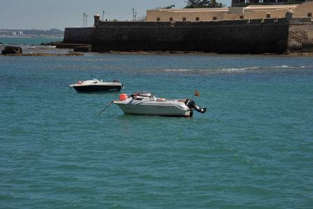 Boats off the coast of Cadiz near the fortress of Castillo Fortaleza de Santa Catalina.