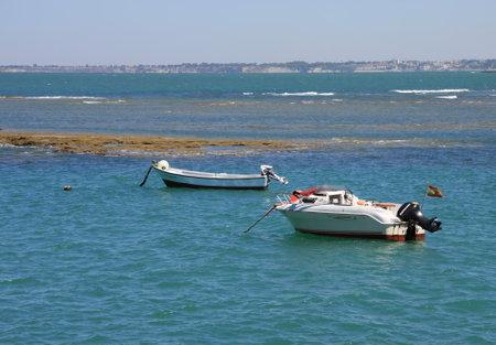 Boats off the coast near the beach of La Catalina in Cadiz. Editorial