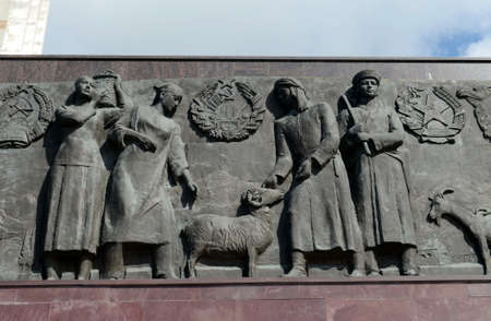 """Sculptural composition-bas-relief at the foot of the monument """"Worker and Collective Farm Girl"""" in Moscow."""