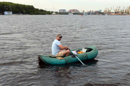 Fisherman in an inflatable boat at the Khimki Reservoir in Moscow