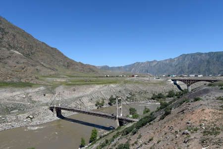 The old and new bridges across the Katun River near the village of Inia on the Chuysk tract in the Altai Republic