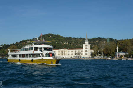Passenger pleasure boat sailing past the building of the Kuleli Military High School on the Asian side of the Bosphorus Strait in Istanbul Banque d'images
