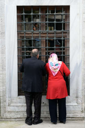 Unidentified people look out the window of the mausoleum of Abdurrahman Pasha in Istanbul