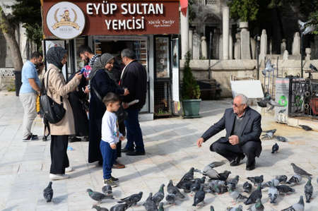 People feed pigeons on Eyup Sultan Square in Istanbul