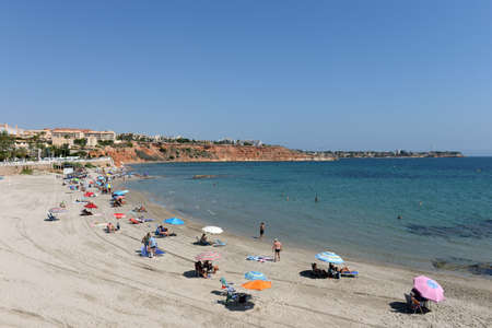 People relax on the sandy beach of Playa de Aguamarina, province of Alicante, Spain