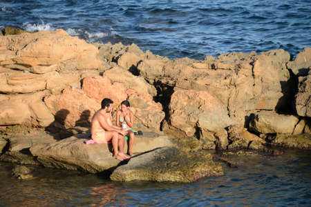 People relax on the rocks of Orihuela, Costa Blanca. Spain