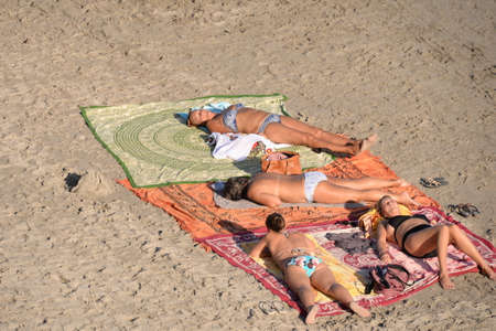 Women sunbathe on the beach in Orihuela Costa. Spain