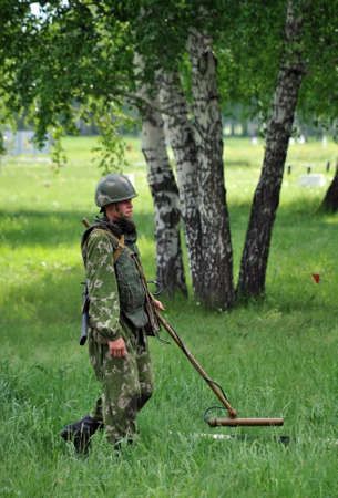 Sapper with a metal detector examines the territory