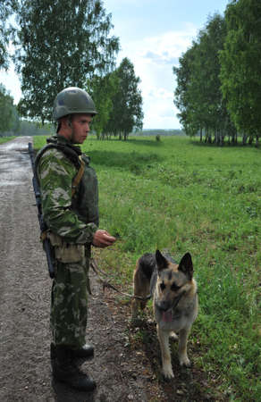 Military dog handler with a Sheepdog to search for explosives