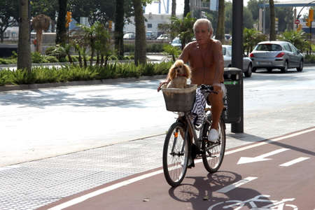 Unknown elderly cyclist rides with a dog on the street of the resort of Malaga