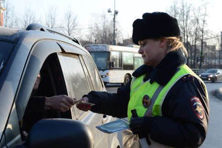 The inspector of the road patrol service of the police checks the documents of the driver of the stopped car Editorial