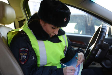The inspector of the road patrol service of the police draws up a protocol on violation of traffic rules Editorial