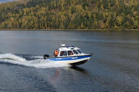 A transport police boat is patrolling the waters of Lake Teletskoye. Altai republic