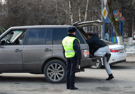 The inspector of the road patrol service of the police checks the trunk of a stopped car