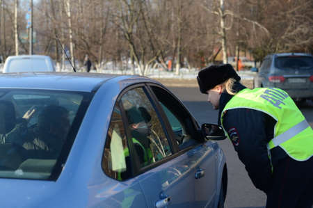 The inspector of the road patrol service of the police speaks with the driver of the stopped car Editorial