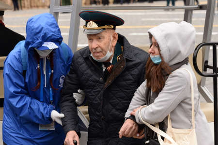Victory Volunteers help a veteran of the Great Patriotic War on Moscow's Red Square during the Victory Day celebration Sajtókép
