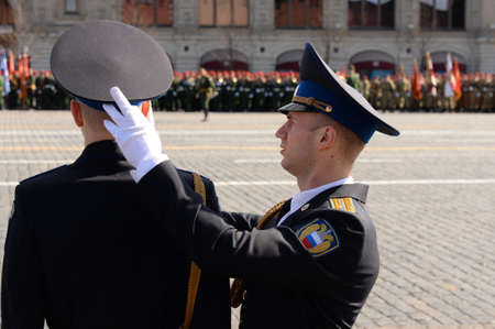 An officer of the presidential regiment adjusts the cap of a soldier during the dress rehearsal of a military parade on Red Square in Moscow