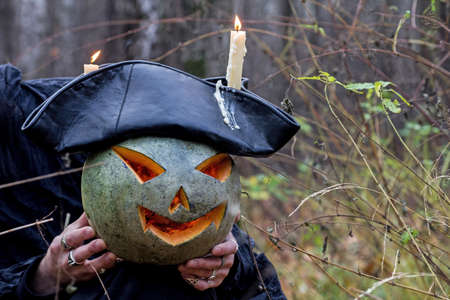 stranger: Stranger with covered face keeps pumpkin on his hands in the forest