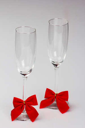 Two glasses of champagne with red bows on a white background photo