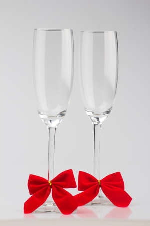 Two glasses of champagne with red bows on a white  photo